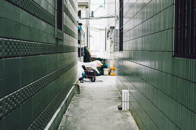 People working in alley amidst buildings