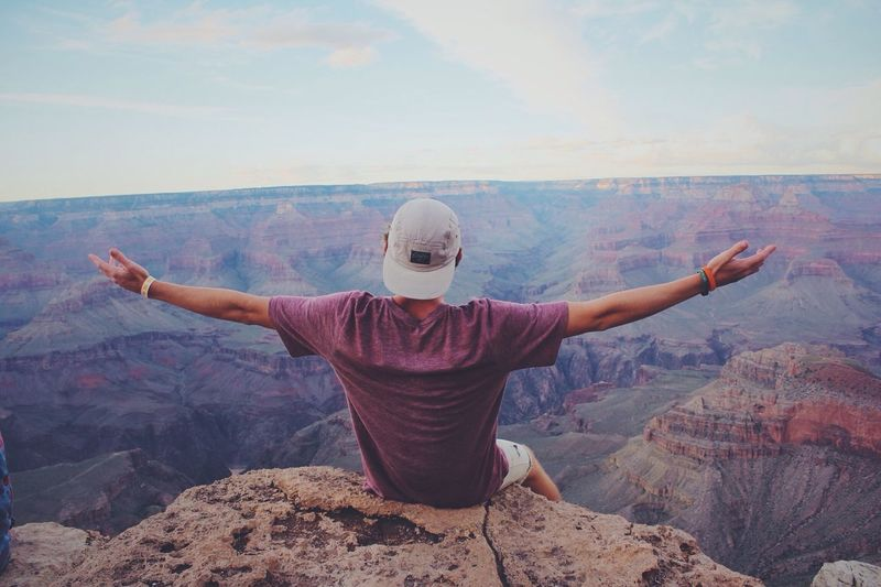 Rear View Of Man Sitting With Arms Outstretched On Rock At Grand Canyon National Park