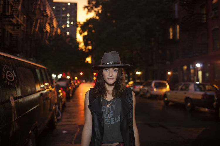 Portrait of young woman standing on illuminated street at night