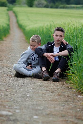 Siblings sitting on field