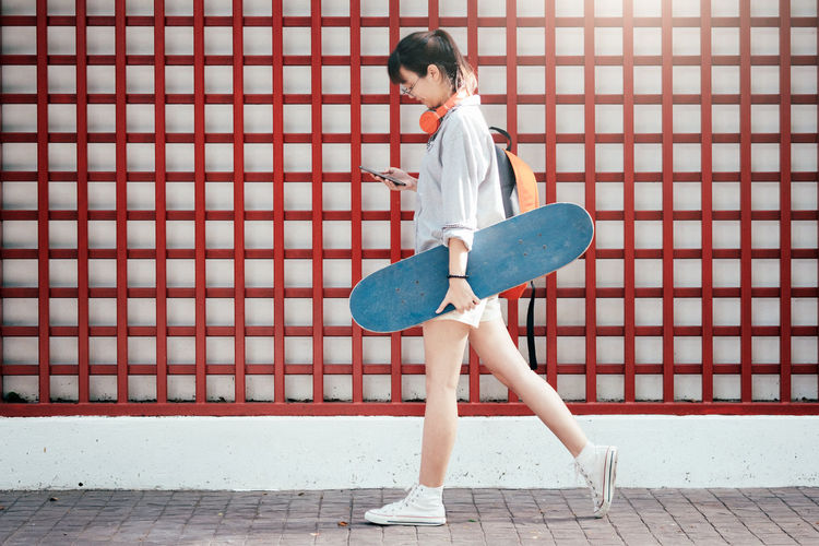 Full Length Of Young Woman With Skateboard Against Patterned Wall