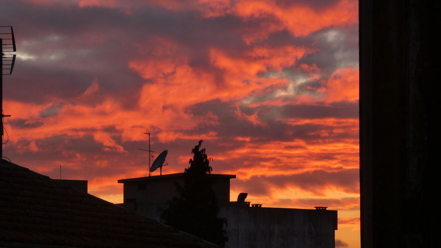 Silhouette of building against cloudy sky during sunset