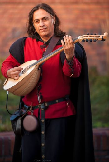 Portrait Of Smiling Man Playing Musical Equipment While Standing Outdoors