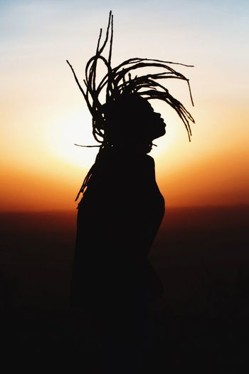 Silhouette Woman Tossing Hair While Standing Against Sky During Sunset