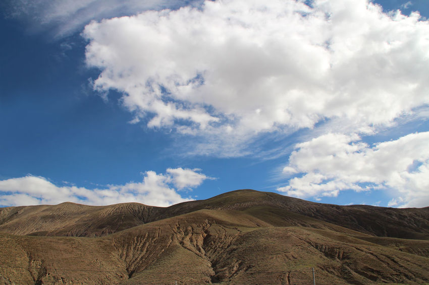 View of the mountains with dramatic sky in Tibet, China Arid Climate Beauty In Nature Blue Cloud - Sky Day Desert Dramatic Sky Environment Landscape Mountain Nature Outdoors Sand Scenics Sky Sun Sunlight And Shadow Sunny Tibet Travel