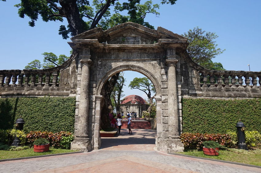 A walk in the park (1) Arch Architecture Building Exterior Built Structure Clear Sky Day Entrance Eyeem Philippines Façade Footpath Gate Grass Here Belongs To Me Incidental People Lifestyles Manila Men Paco Park Person Sky Sunlight Tree Walking Miles Away The Secret Spaces