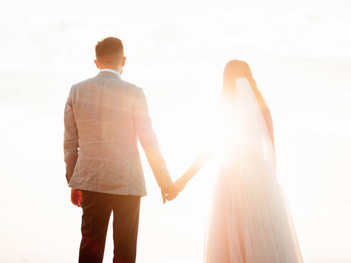Rear View Of Newlywed Couple Standing Against Sky