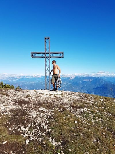 Shirtless man standing by cross on mountain against clear blue sky