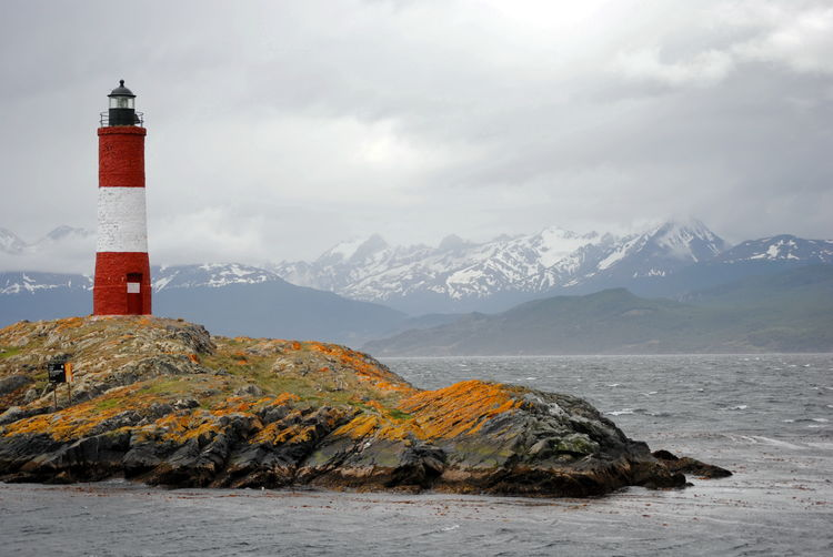 Red and white lighthouse in the Beagle Channel, Ushuaia, Tierra del Fuego, Argentina. People call it End of the world's lighthouse. It's name is Les Eclaireus. Lighthouse Tower Sky Water Security Guidance Protection Sea Architecture Safety Built Structure Building No People Outdoors Ushuaïa Beagle Channel Red Ocean Wave Island Eclaireurs End Colors Patagonia Argentina