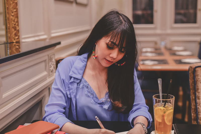 Woman writing in diary while sitting in restaurant