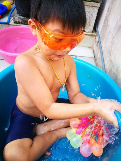 High Angle View Of Boy Playing With Water Bombs In Basket