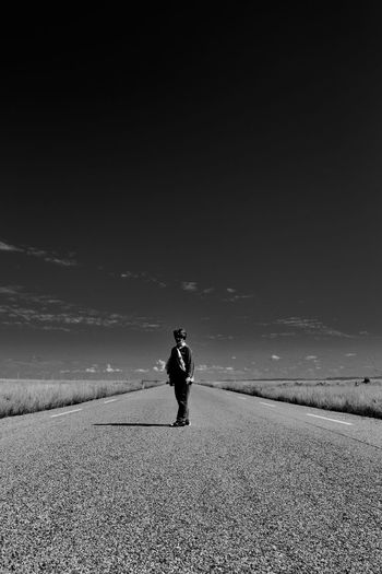 Full length of man walking on road against sky