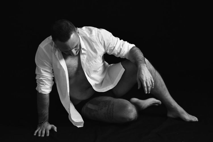 Midsection of man sitting against black background