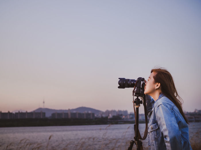 Hipster woman photographer during setting and take photo by her camera to river during sunset