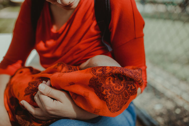 Midsection of woman breastfeeding baby outdoors