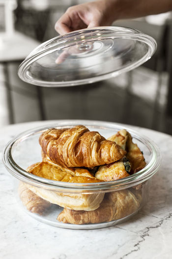 Cropped hand holding lid over container with croissants on table