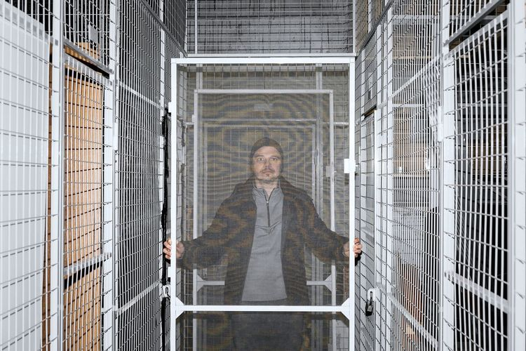 Portrait of man standing by fence in underground