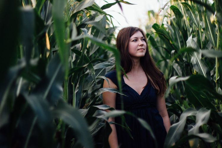 Young woman standing amidst corn crops on field