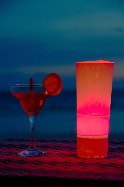 Cocktail at the beach Beach Beverage Blue Candle Close-up Cocktail Drinking Straw Focus On Foreground Freshness Glass Lamp Lemon Light Night No People Pink Color Red Refreshment Selective Focus Sky Still Life Summer