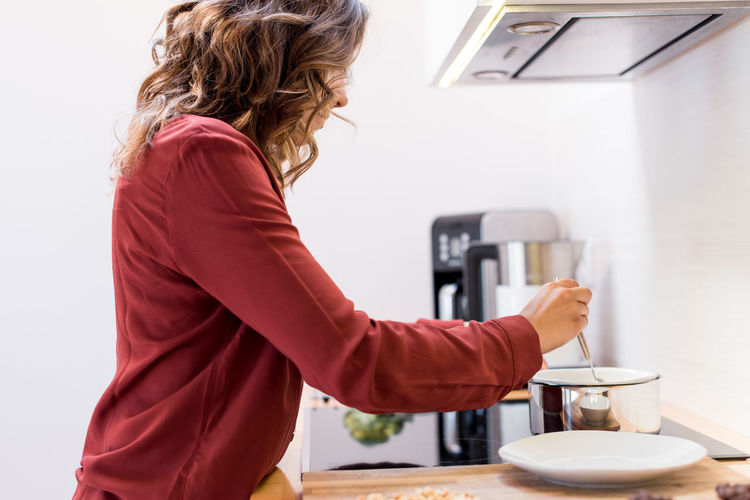 Side view of woman holding coffee cup