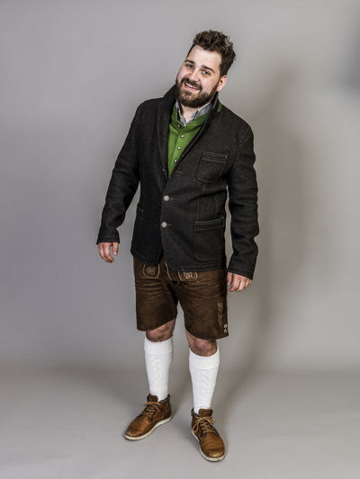 Man Traditional Costume Disguise Custom Customs Austria Rural Leather Trousers Socks Jacket Green Grey Posen Model Male One STAND Copy Space Cool Beard Unshaven Joy Laugh Happy Robe Fashion Party Uniform Masked Ball Masquerade Beautiful Warm Summer Buttons Modern Rustic Vest Pattern One Person Studio Shot Front View Young Adult Full Length Portrait Looking At Camera Indoors  Standing Clothing Young Men Casual Clothing Shoe Gray Gray Background Smiling Real People Jeans Scarf