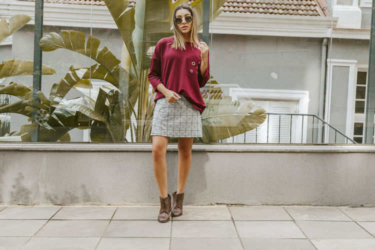 Full Length Of Fashionable Young Woman Standing On Footpath In City
