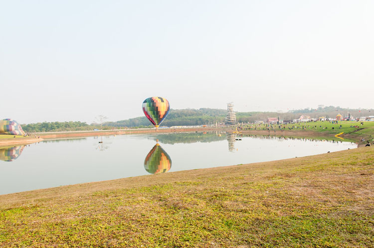 Balloon in the sky. ( sky not bright and Cloudy skies) Balloon Ballooning Festival Clear Sky Day Grass Hot Air Balloon Lake Landscape Nature No People Outdoors Sky Transportation Water