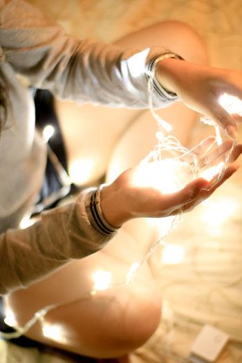 Close-up of woman holding illuminated string light