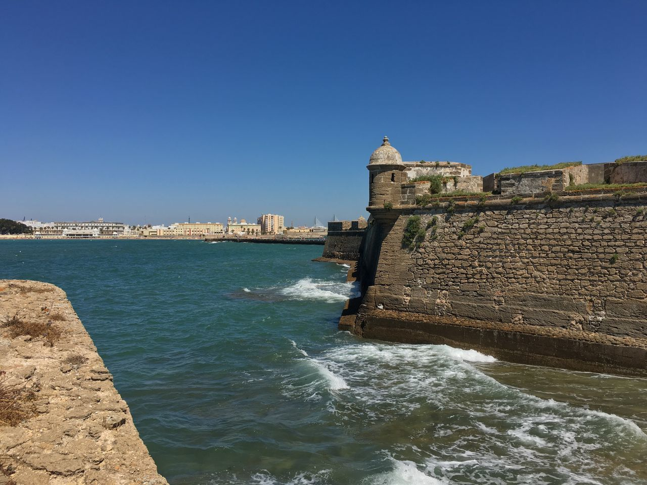 architecture, water, built structure, history, building exterior, sea, copy space, fort, day, travel destinations, outdoors, clear sky, castle, no people, blue, nature, city, beauty in nature, sky