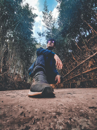 Low angle view of young man in forest