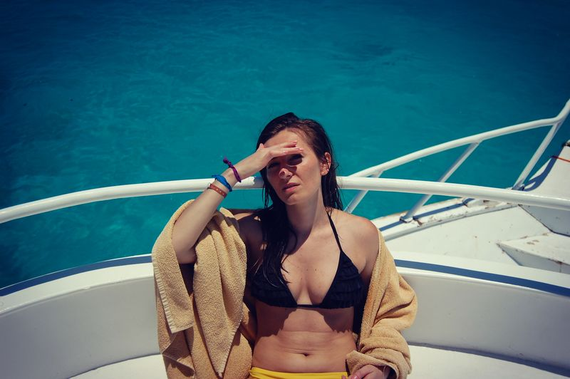 Beautiful woman shielding eyes with hand while sitting in yacht on sunny day