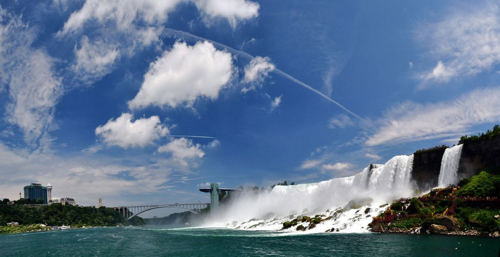 Scenic view of waterfall by bridge against sky