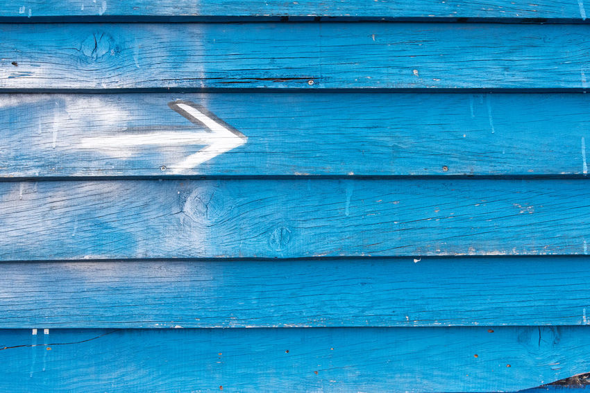 Information Wood - Material Blue Full Frame Backgrounds No People Pattern Day Outdoors Close-up Plank Built Structure Old Architecture Textured  Wall - Building Feature White Color Door Paint Wood Entrance Garage Arrow Symbol Arrow Sign Arrow Painted Wooden Worn Out Hardwood Shutter