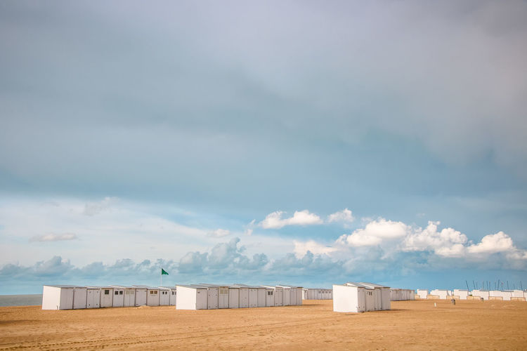 Scenic view of beach huts against sky
