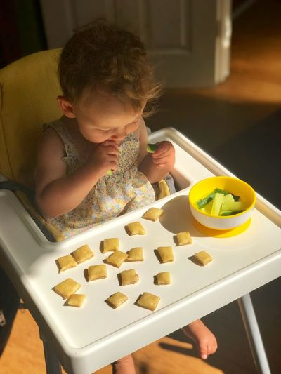 High angle view of cute baby girl eating food while sitting on high chair at home