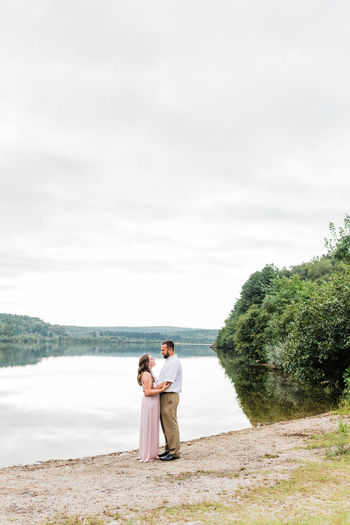 Rear view of couple standing on shore against sky