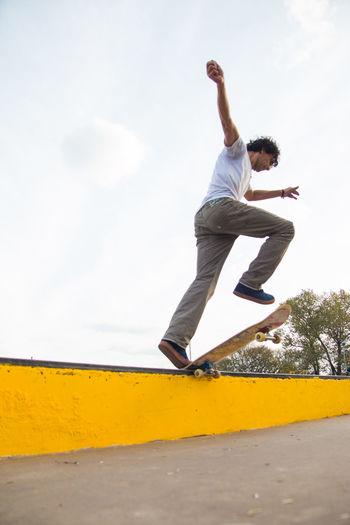 Full length of man jumping against sky