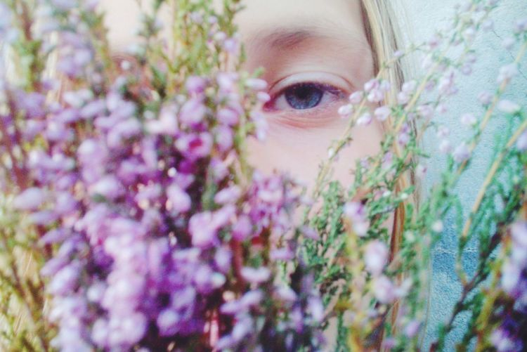 Close-Up Of Girl Behind Flowers