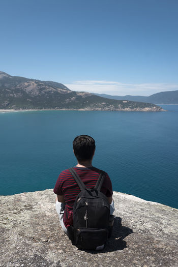 Shot at Wilsons Promontory, Gippsland. Adventure Backpack Beauty In Nature Clear Sky Day Lake Leisure Activity Lifestyles Looking At View Men Mountain Mountain Range Nature One Person Outdoors Real People Rear View Relaxation Scenics Sitting Sky Tranquil Scene Tranquility Vacations Water