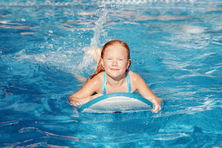 Portrait of smiling girl swimming in pool