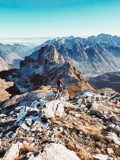 Midsection of person on rock by snowcapped mountain against sky