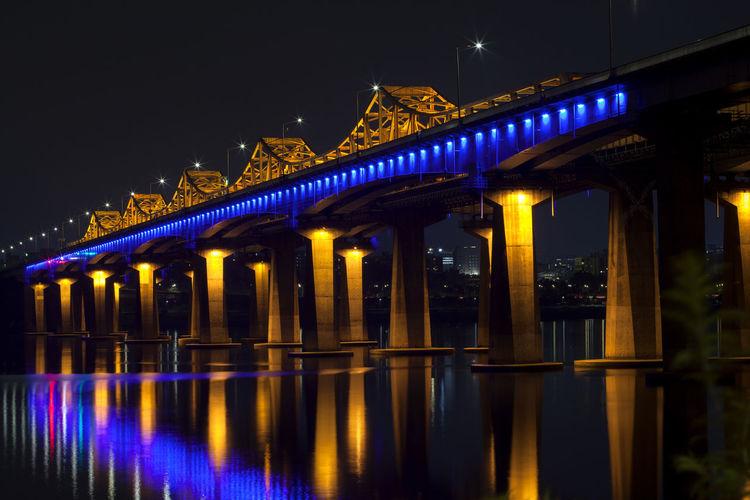 Reflection of illuminated bridge on han river at night