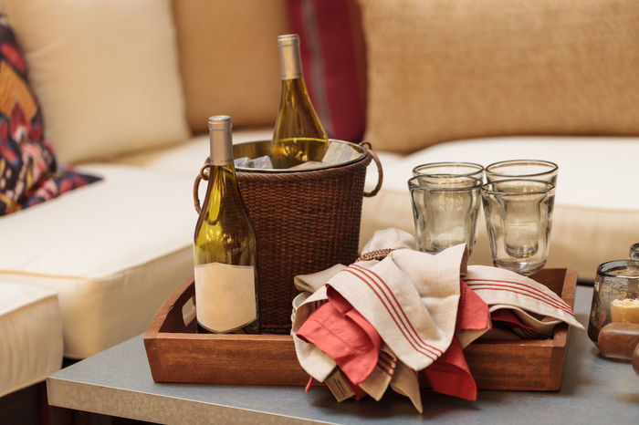 Ice bucket, bottle of white wine, red and white napkins, wine glasses on tray on a rustic patio table in summer. Decoration Glass Ice Bucket Indoors  Liqueur Liqueur Bottle Livingroom Livingroom Decor Napkin No People Picnic Tray Wine Wine Bottle Wine Glasses