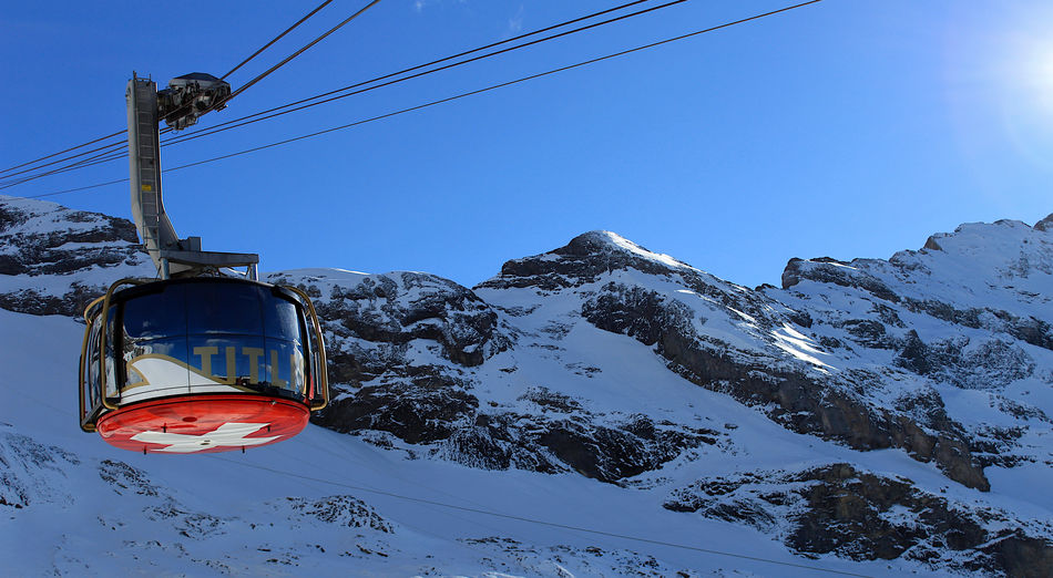 Overhead cable car in snow covered mountains against sky