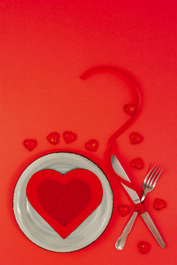 Directly above shot of heart shape on red table
