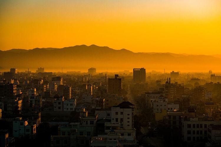 Cityscape against sky during sunrise.