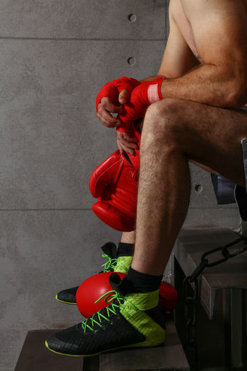 Low section of shirtless man holding gloves while sitting on steps