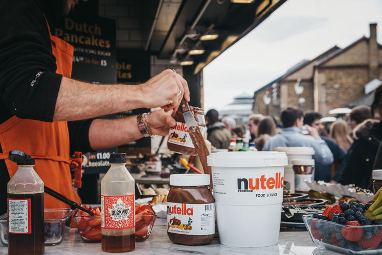 Staff cooking Dutch pancakes at a stall inside Camden Market, London. Started with 16 stalls in 1974, Camden Market is one of the busiest retail destinations in London. Berries Condiments  Syrup Chocolate Spread Nutella Consumerism Drink Lifestyles Architecture Text Outdoors Freshness Human Hand Retail  Incidental People Day Holding Focus On Foreground One Person Men Container Food Food And Drink Real People Tourists People Leisure Activity Travel Destinations Europe England Market Famous Place Weekend Activities Trabel Camden Market, London Camden Town Uk London Retail  Standing