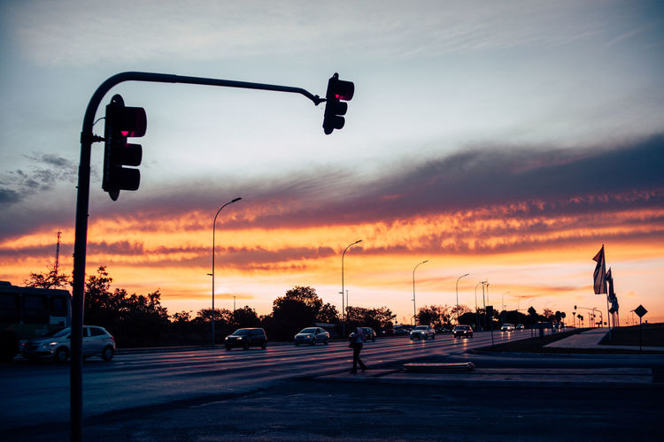 Silhouette Traffic Signal On Road Against Cloudy Sky During Sunset