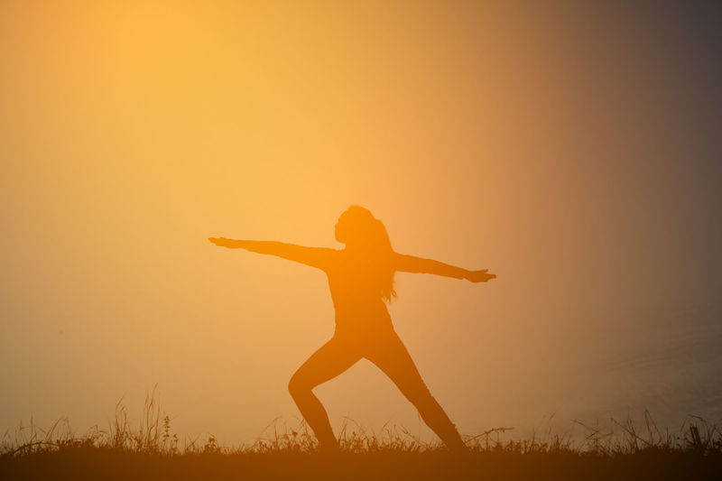 Silhouette woman exercising warrior 2 on field